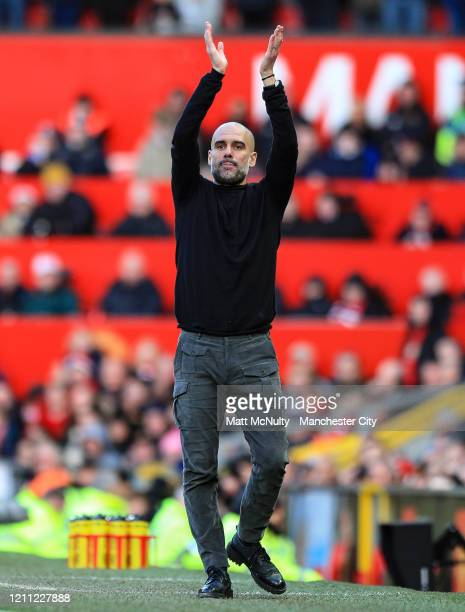 Pep Guardiola Manager of Manchester City applauds his players during the Premier League match between Manchester United and Manchester City at Old...