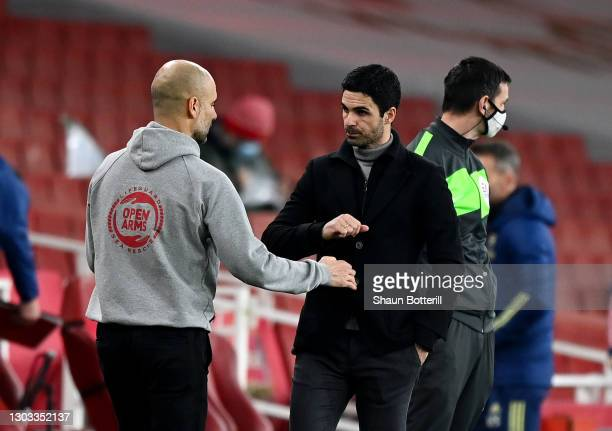 Pep Guardiola, Manager of Manchester City bumps fists with Mikel Arteta, Manager of Arsenal after the Premier League match between Arsenal and...