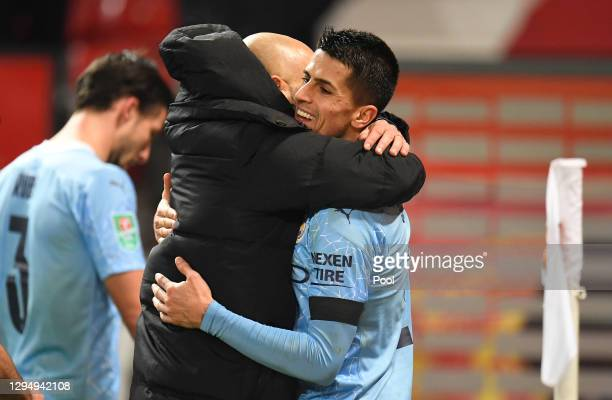 Pep Guardiola, Manager of Manchester City embraces Ferran Torres of Manchester City after the the Carabao Cup Semi Final match between Manchester...