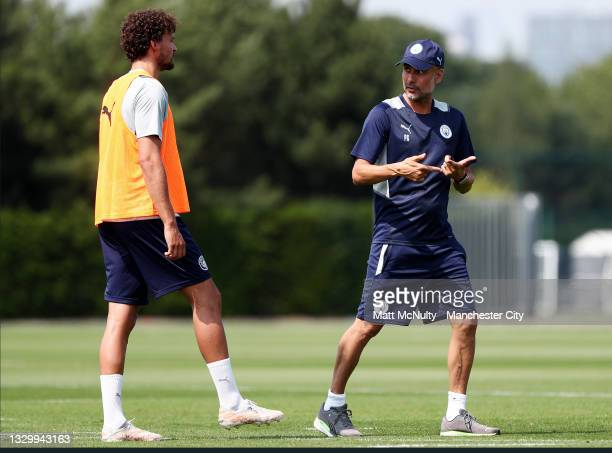 Pep Guardiola, manager of Manchester City gives instructions to Phillipe Sandler of Manchester City during a training session at Manchester City...