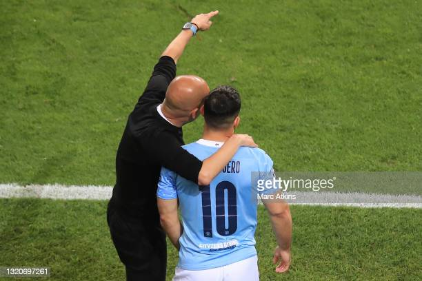 Pep Guardiola, Manager of Manchester City gives instructions to Sergio Aguero of Manchester City as he prepares to be substituted on during the UEFA...