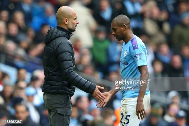 Pep Guardiola, Manager of Manchester City greets Fernandinho of Manchester City as he leaves the pitch after receiving a red card during the Premier...