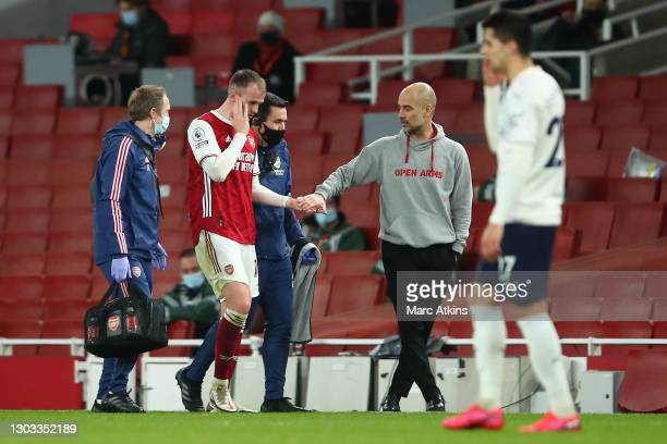 Pep Guardiola, Manager of Manchester City greets Rob Holding of Arsenal as he is substituted off due to a head injury during the Premier League match...