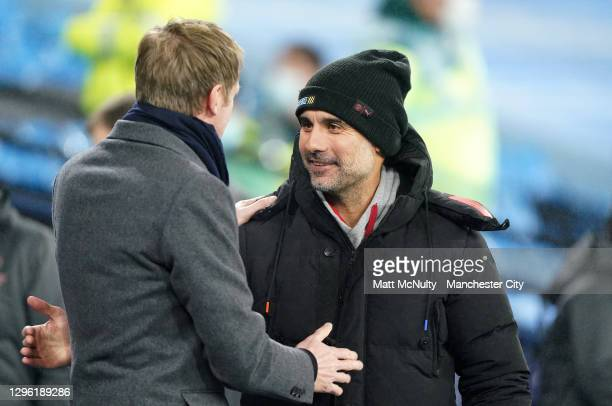 Pep Guardiola, Manager of Manchester City interacts with Graham Potter, Manager of Brighton and Hove Albion prior to the Premier League match between...