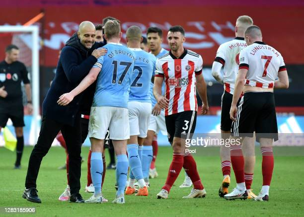 Pep Guardiola, Manager of Manchester City interacts with Kevin De Bruyne of Manchester City after the Premier League match between Sheffield United...