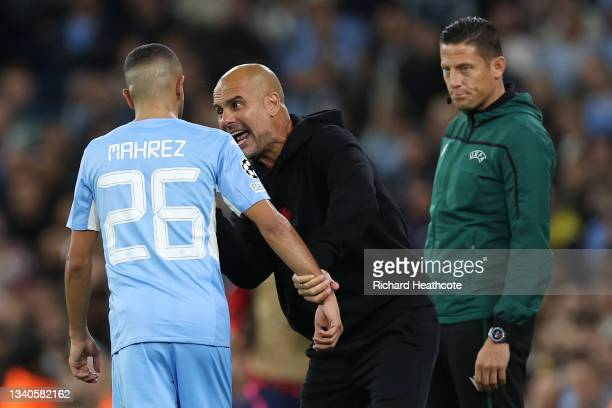 Pep Guardiola, Manager of Manchester City interacts with Riyad Mahrez of Manchester City during the UEFA Champions League group A match between...
