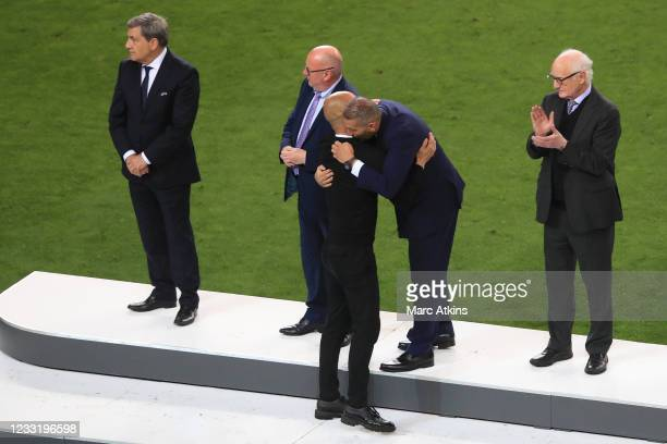 Pep Guardiola manager of Manchester City is embraced by Chairman Khaldoon Al Mubarak as Bruce Buck, Chelsea chairman looks on during the UEFA...