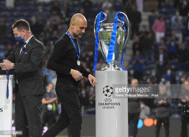 Pep Guardiola, Manager of Manchester City looks dejected as he walks past the Champions League Trophy after the UEFA Champions League Final between...