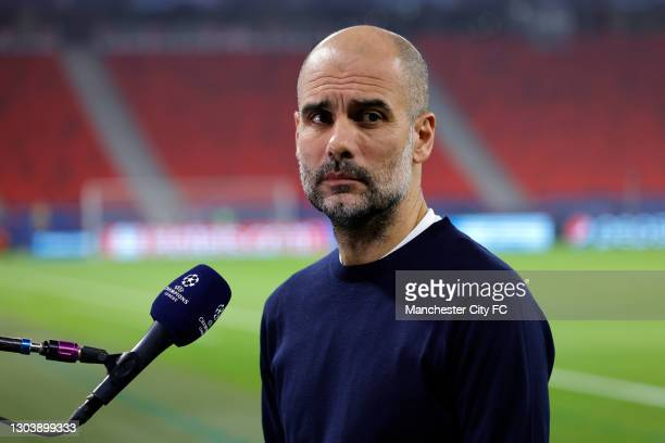 Pep Guardiola, Manager of Manchester City looks on as he is interviewed prior to the UEFA Champions League Round of 16 match between Borussia...