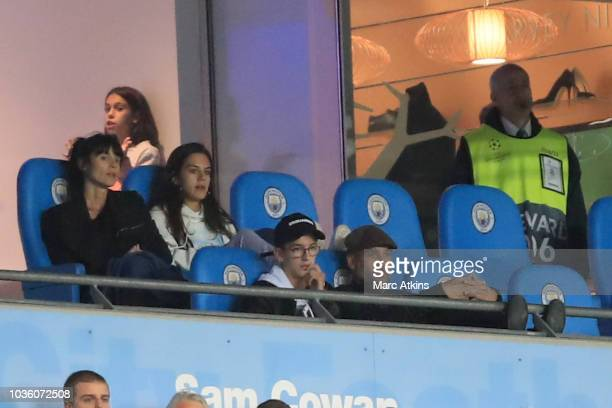 Pep Guardiola manager of Manchester City looks on as he saves a touchline ban surrounded by his family during the Group F match of the UEFA Champions...