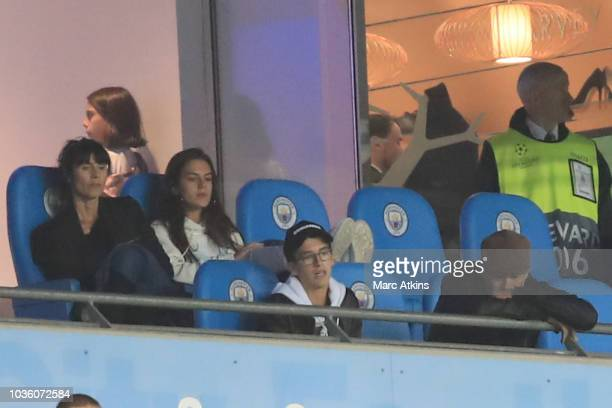 Pep Guardiola manager of Manchester City looks on as he serves a touchline ban surrounded by his family during the Group F match of the UEFA...