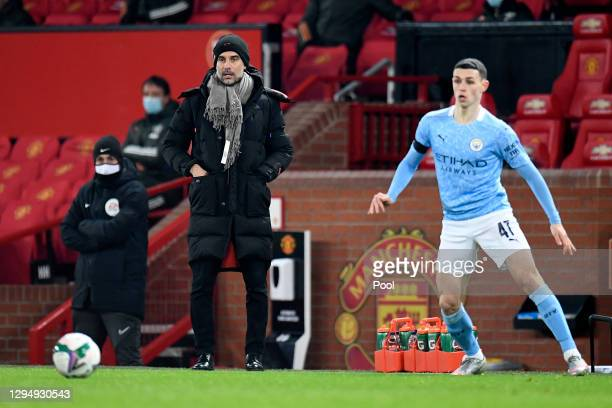 Pep Guardiola, Manager of Manchester City looks on as Phil Foden of Manchester City controls the ball during the Carabao Cup Semi Final match between...