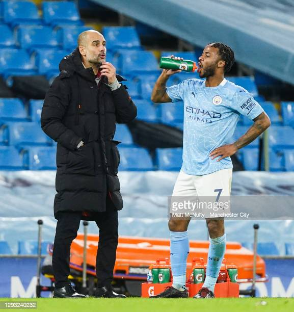 Pep Guardiola, manager of Manchester City looks on as Raheem Sterling takes a drink during the Premier League match between Manchester City and...