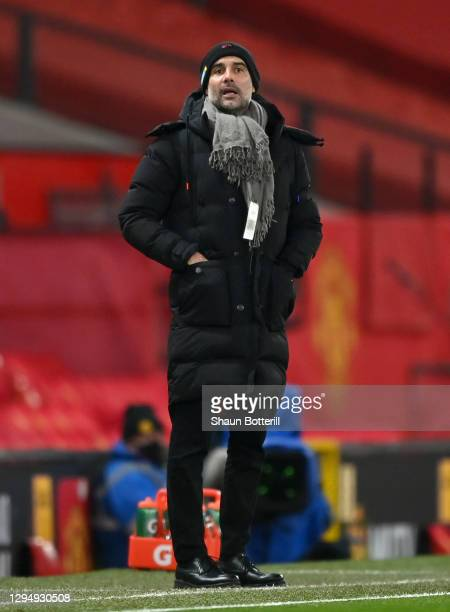 Pep Guardiola, Manager of Manchester City looks on during the Carabao Cup Semi Final match between Manchester United and Manchester City at Old...