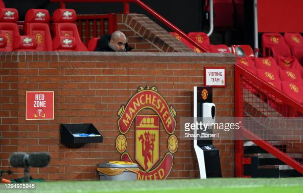 Pep Guardiola, Manager of Manchester City looks on from the bench as his team warms up ahead of the Carabao Cup Semi Final match between Manchester...