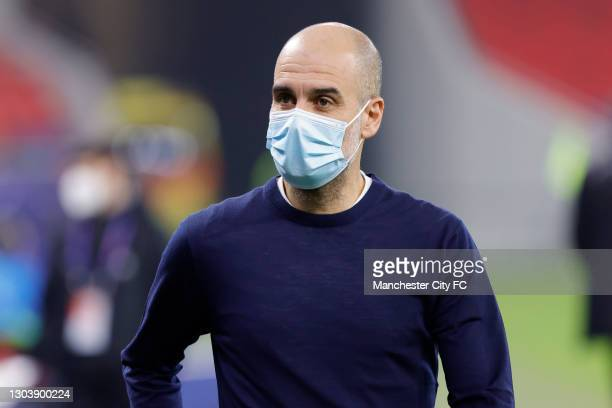 Pep Guardiola, Manager of Manchester City looks on whilst wearing a face mask prior to the UEFA Champions League Round of 16 match between Borussia...