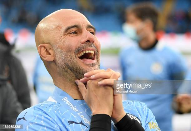 Pep Guardiola, Manager of Manchester City reacts after Manchester City are presented with the Premier League Trophy as they win the league following...