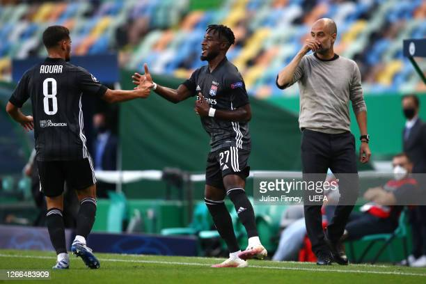 Pep Guardiola, Manager of Manchester City reacts as Maxwel Cornet of Olympique Lyon celebrates with teammate Houssem Aouar after scoring his team's...