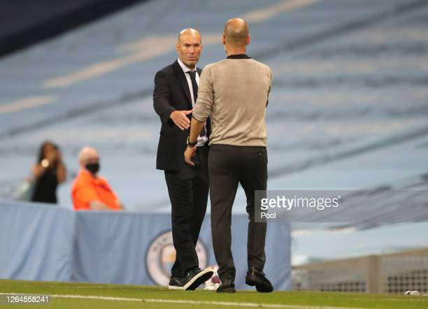 Pep Guardiola Manager of Manchester City shakes hands with Zinedine Zidane Head Coach of Real Madrid following the UEFA Champions League round of 16...