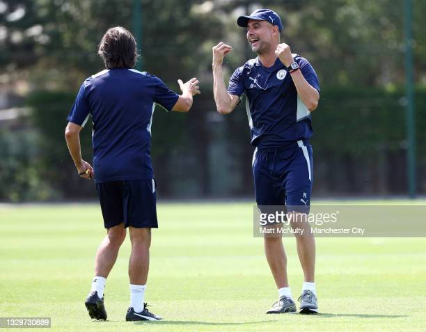 Pep Guardiola, manager of Manchester City shares a joke with his coach, Lorenzo Buenaventura during a training session at Manchester City Football...
