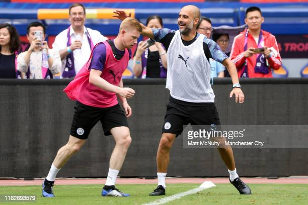 Pep Guardiola, manager of Manchester City shares a joke with Kevin de Bruyne during the training session at Nanjing Olympic Sports Centre on July 18,...