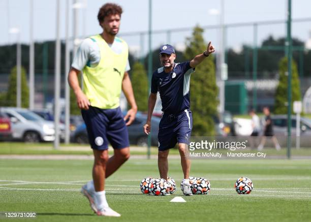 Pep Guardiola, manager of Manchester City shouts instructions to Phillipe Sandler of Manchester City in action during a training session at...