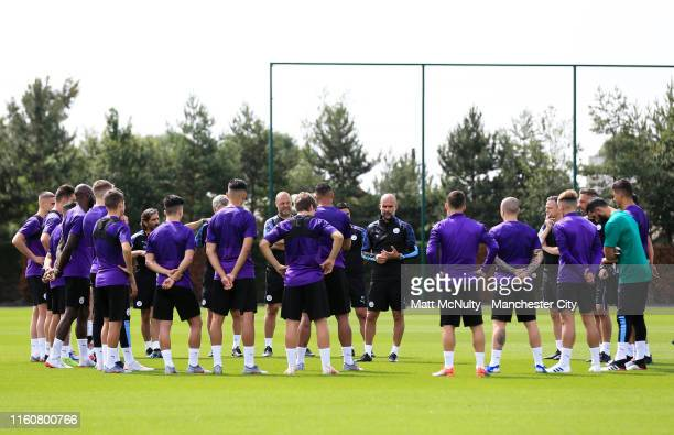 Pep Guardiola manager of Manchester City speaks with his players during the training session at Manchester City Football Academy on July 08 2019 in...