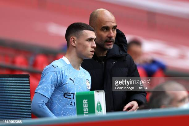 Pep Guardiola, Manager of Manchester City speaks with Phil Foden of Manchester City as he prepares to be substituted on during the Semi Final of the...