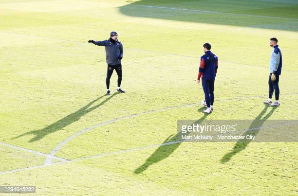 Pep Guardiola, manager of Manchester City speaks with Ruben Dias and Zack Steffen during a training session at Manchester City Football Academy on...