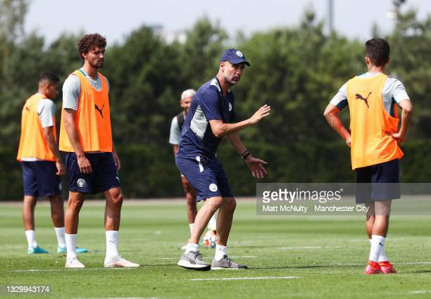 Pep Guardiola, manager of Manchester City talks to his players during a training session at Manchester City Football Academy on July 20, 2021 in...
