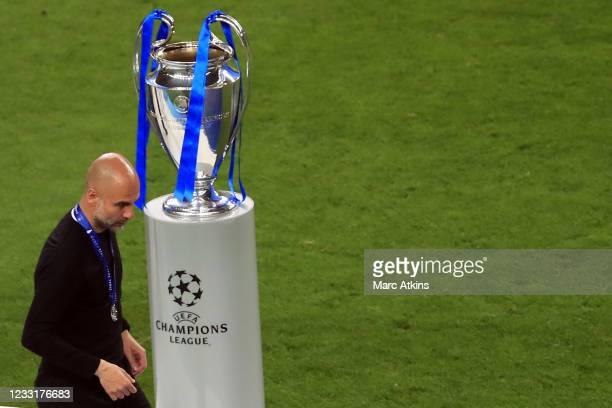 Pep Guardiola manager of Manchester City walks past the Champions League trophy after collecting his runners up medal during the UEFA Champions...