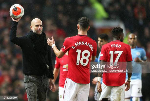 Pep Guardiola Manager of Manchester United hands the ball to Bruno Fernandes of Manchester United during the Premier League match between Manchester...
