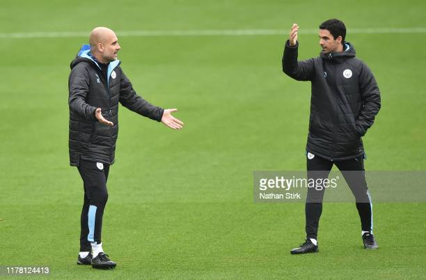 Pep Guardiola of Manchester City talks to Mikel Arteta Assistant Manager of Manchester City during a training session at Manchester City Football...