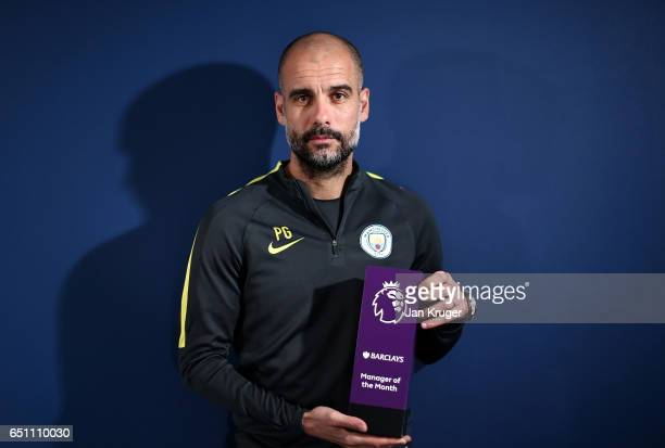 Pep Guardiola poses with the Barclays Manager of the Month Award for February at Etihad Campus on March 7 2017 in Manchester England