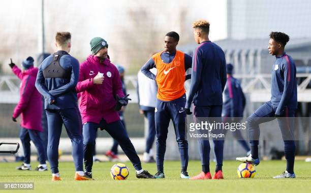 Pep Guardiola talks with Luke Bolton Nathanael Ogbeta Felix Nmecha and Keke Simmonds during training at Manchester City Football Academy on February...