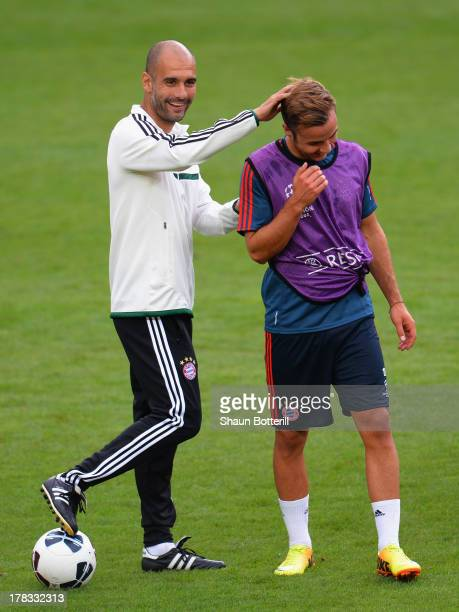 Pep Guardiola the FC Bayern Munchen coach shares a joke with player Mario Gotze during a training session prior to the UEFA Super Cup match between...