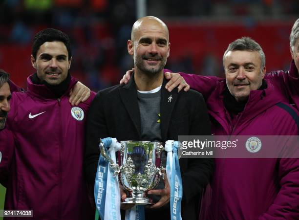 Pep Guardiola the head coach / manager of Manchester City celebrates with the trophy and assistants Mikel Arteta and Domenec Torren after winning the...
