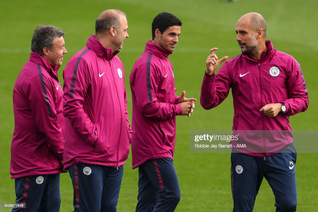 Pep Guardiola the head coach / manager of Manchester City gestures towards his coaching staff during a Press Conference and Training Session at Manchester City Football Academy on April 9, 2018 in Manchester, England.