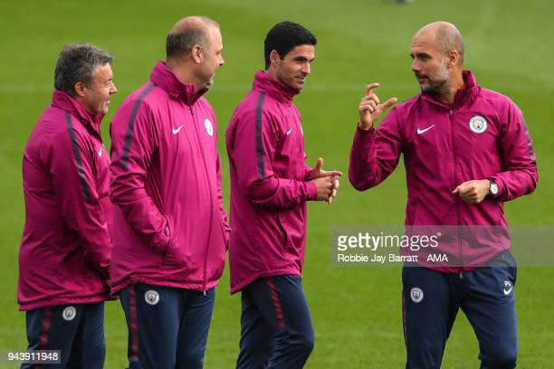 Pep Guardiola the head coach / manager of Manchester City gestures towards his coaching staff during a Press Conference and Training Session at...