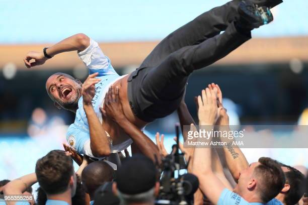 Pep Guardiola the head coach / manager of Manchester City gets thrown into the air during the championship celebrations after the Premier League...
