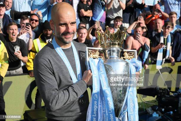 Pep Guardiola the head coach / manager of Manchester City shows the Premier League Trophy to fans of Manchester City during the celebrations of...