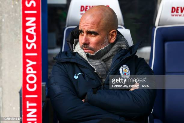 Pep Guardiola the head coach / manager of Manchester City sits in the dugout prior to the Premier League match between Huddersfield Town and...