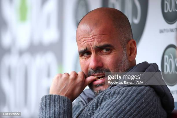 Pep Guardiola the head coach / manager of Manchester City sits in the dugout prior to the Premier League match between Burnley FC and Manchester City...