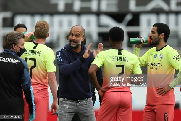 Pep Guardiola the head coach / manager of Manchester City speaks to Raheem Sterling of Manchester City during the FA Cup Quarter Final match between...
