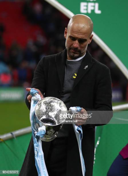 Pep Guardiola the head coach / manager of Manchester City with the trophy and wearing a yellow ribbon after winning the Carabao Cup Final between...