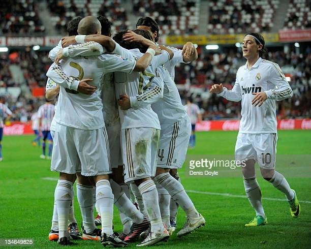 Pepe and Mesut Ozil of Real Madrid celebrate with teammates after Real scored their second goal during the La Liga match between Sporting Gijon and...