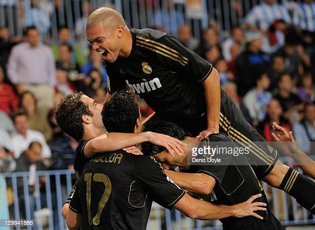Pepe and Real Madrid teammates celebrate their opening goal during the La Liga match between Malaga CF and Real Madrid CF at Estadio La Rosaleda on...