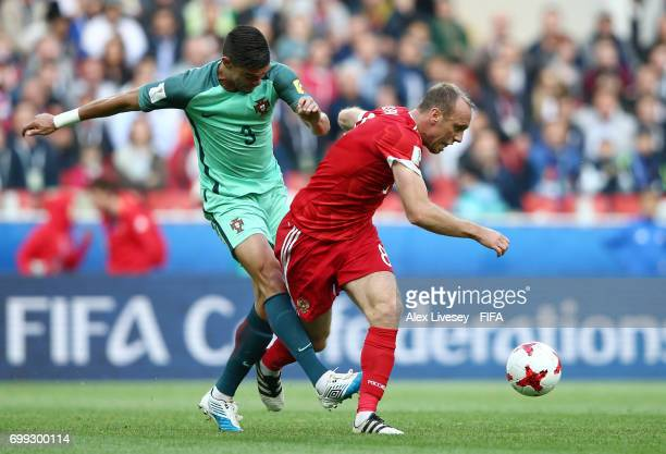 Pepe of Portugal and Dennis Glushakov of Russia battle for possession during the FIFA Confederations Cup Russia 2017 Group A match between Russia and...