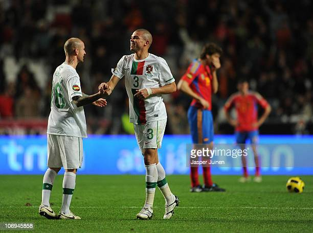 Pepe of Portugal celebrates his sides fourth goal with his teammate Raul Meireles of Portugal as Fernando Llorente of Spain stand dejected waiting to...