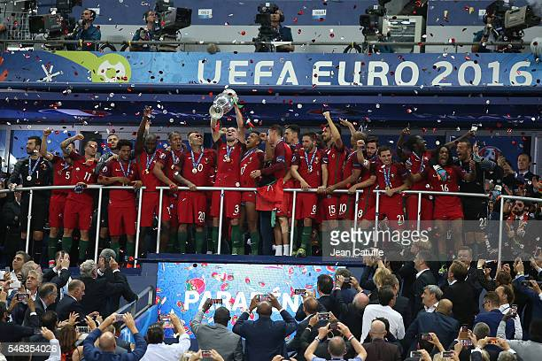 Pepe of Portugal holding the trophy and teammates celebrate the victory during the trophy ceremony following the UEFA Euro 2016 final between...